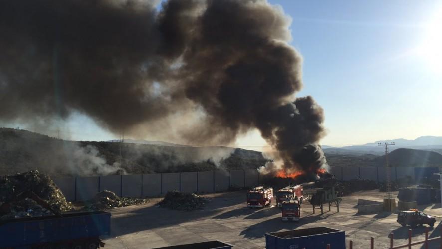 Bomberos trabajan en el incendio del solar de una nave de chatarra en Molina
